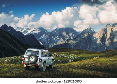Landscape view of mountain range and offroad car in the meadow, Svaneti national park, Country of Georgia