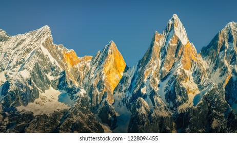Landscape view of mountain range and peaks lit by golden sunlight, Himalayas, Nepal, Asia