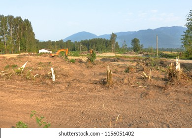 Landscape view of a new residential subdivision taking shape after trees have been cleared and industrial equipment has started work.