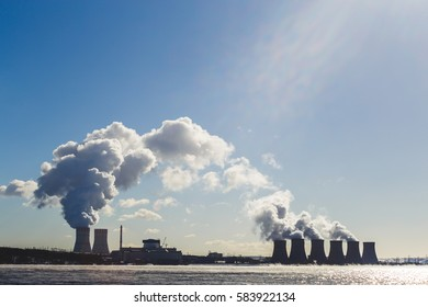 Landscape with view of Nuclear power Plant from cooling pond. Clouds of thick smoke on blue sky background at Sunny day. Copy space