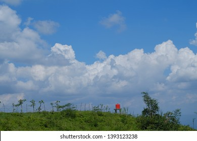 landscape view on the hill with blue sky and white clouds also orange watter torrent