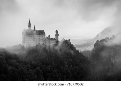 Landscape view on Neuschwanstein Castle, the 19th century Romanesque Revival palace, on the foggy day in southwest Bavaria, Germany