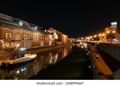 "Landscape view of Otaru canals and warehouse at night in Hokkaido Japan. Here is a famous landmark of Otaru city. Text in Japanese is ""Otaru storehouse""."
