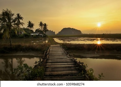 Landscape view of paddy fields,small village,mountain,bridge,river during sunset.