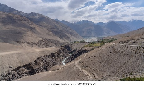 Landscape view of Pamir river gorge in high altitude desert bordering Afghanistan with Hindu Kuch mountain range in background, Wakhan Corridor, Gorno-Badakshan, Tajikistan - Shutterstock ID 2019300971