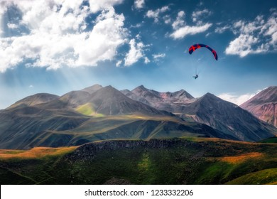 Landscape view of paraglider flying over beautiful mountains and sky with sunrays, Kazbegi, Country of Georgia