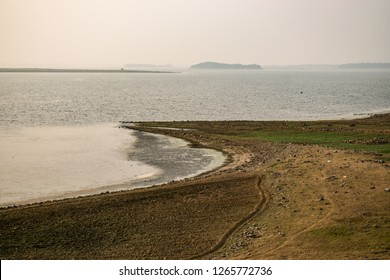 """Landscape view of partial river bank of """"Kumari"""" river, vast water body and small distant foggy islands within it. Mukutmanipur, Bankura, West Bengal."""