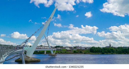 Landscape view of the Peace Bridge found in Londonderry with the white clouds in the sky