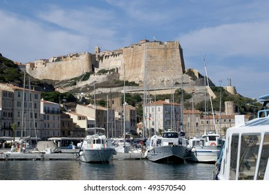 Landscape view of the port of Bonifacio, with yachts, boats, pier and buildings, overlooked by ancient Bastion de l'Etendard; Bonifacio (Bunifaziu), Corsica, France; 08/09/2014