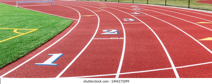Landscape view of a red track with white numbers that have blue trim at the two hundred meter start.