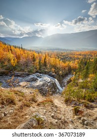 Landscape view of Risjok waterfall with a northern taiga forest in the background at the bright sunny afternoon, Hibiny mountains above the Arctic circle, Russia