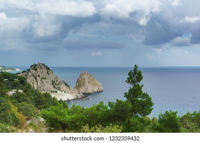 Landscape view of the rocks of Panea and Diva, protruding into the calm Black sea. Pine and juniper trees grow on the shore in Simeiz village. Crimea, Yalta, Russia