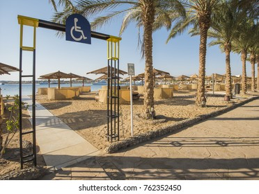 Landscape view of a sandy beach with disabled access and sunbeds at tropical luxury hotel resort