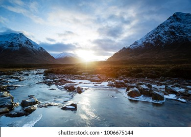 landscape view of scotland and the entrance to glen etive in winter with a frozen river in the foreground