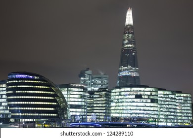 A landscape view of The Shard in London at Night sitting behind City Hall