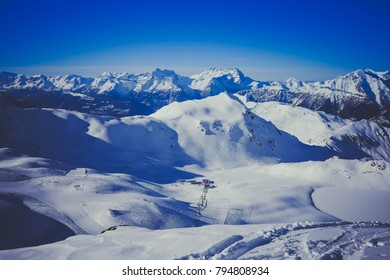 "landscape view of the ski resort of ""Verbier"" in Switzerland with the slopes and snowy mountains in the background"