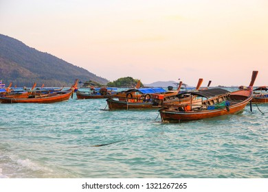 Landscape view of sunrise with wooden boats on sea beach at Lipe island, Satun province, Thailand.