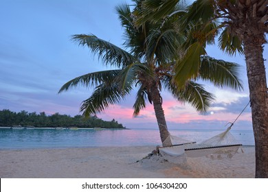 Landscape view of sunset over Muri lagoon with empty hammock hanged on coconut palm trees on a pacific tropical island of Rarotonga, Cook Islands.
