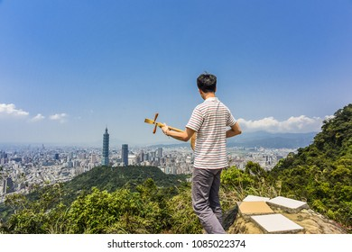 Landscape View Of Taipei City with Young People Playing Traditional Chinese Instrument on The Top of Thumb Mountain, Taipei City, Taiwan