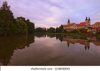 Landscape view of Telc castle, lake, Name of Jesus Church and tower of the Church of St. Jakub. Buildings are reflected in the water. A UNESCO World Heritage Site.