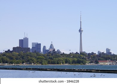 A landscape view of the Toronto Skyline from the west across Lake Ontario.  Visible landmarks include High Park, CN Tower, First Canadian Place, Scotiabank Tower, TD Centre, BCE Place, and CIBC Tower