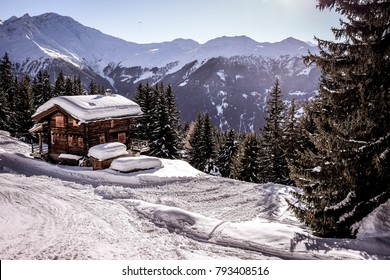 """landscape view of a traditional wooden Swiss chalet, with snowy Alps and forests in the background, in the ski resort of """"Verbier"""" in Switzerland"""