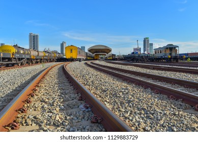 Landscape view of train parking on railway with blue sky at train maintenance shop and building of city in background