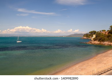 Landscape view of tranquil calm sea in Tuscany gulf, Italy, empty beach and sailbot in sunny day no people