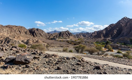 Landscape view of Wadi Shawka  dry riverbed with Emirates Adventures camp buildings, rocky Hajar Mountains in the background, United Arab Emirates.