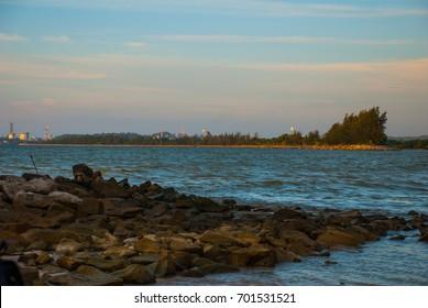 Landscape view of the water in the evening pipe with the fire on the horizon, city Bintulu, Borneo, Sarawak, Malaysia, Pantai Temasya Tanjung Batu