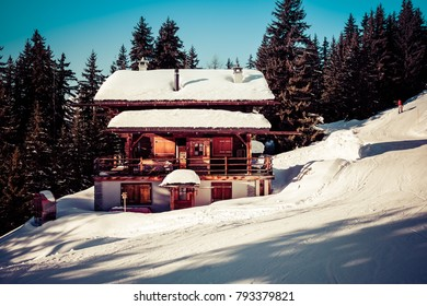 Landscape View Of A Wooden Swiss Chalet With Snow On The Roof And Pine