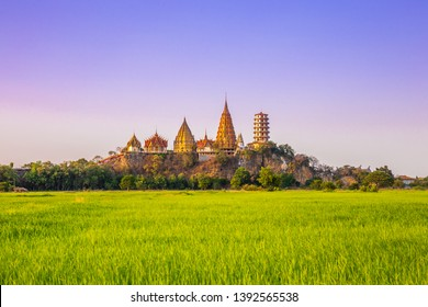 Landscape of Wat Tham Sua Temple (Tiger Cave Temple) in Sunset scence with Jasmine rice fields at Kanchanaburi Province, Thailand. Is an important landmark that everyone must visit