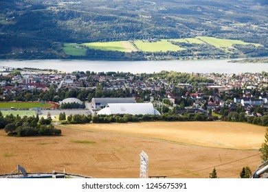 Landscape with wheat field, river and houses in Norwegian Lillehammer town.