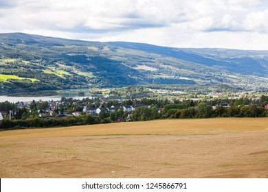 Landscape with wheat field, river and mountains in Norwegian Lillehammer town.