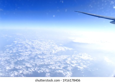 Landscape of white clouds floating above blue sky background. viewed from high altitude. Viewed from airplane window.