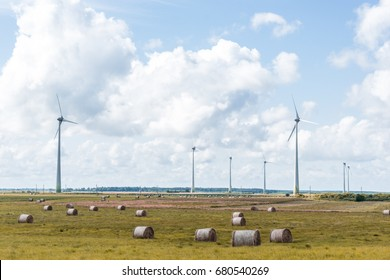 landscape with wind power mills and hay rolls