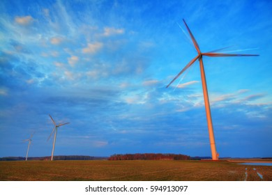 Landscape - The wind power stations in early spring field. Eastern part of Poland, Europe. Sunset or sundown