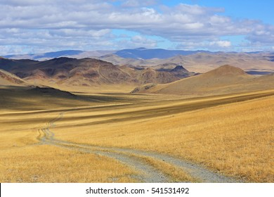Landscape of winding dirt road through rolling hills of Western Mongolian steppe