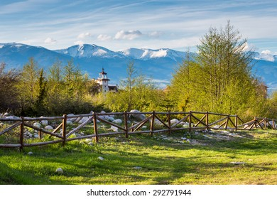 Landscape with the wooden fence, Vibrant spring trees, part of the wooden tower of chalet and snowy peaks of mountains in Bansko, Bulgaria