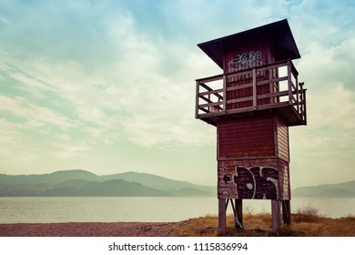 Landscape with wooden lookout tower on lake and mountains background. Beach on a cloudy day. Lonely place for a relaxing vacation.