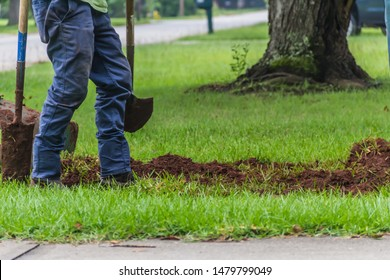 A landscape worker digging a trench during an irrigation system installation project in a yard by a quiet residential street