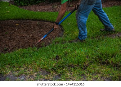 A landscape worker digs in a flower bed with a shovel on a landscaping job site