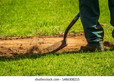A landscape worker using a shovel to level out ground in preparation for laying new sod