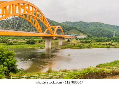 Landscape of yellow arched railroad bridge spanning a river in the countryside on a cloudy overcast day.