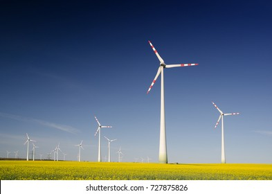 Landscape with yellow flowering rape field and group of wind turbines - clean energy production