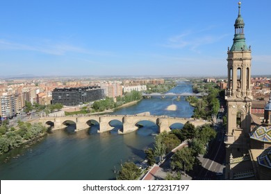 A landscape of Zaragoza with the Puente de Piedra and Puente de Hierro bridges, the Ebro river and a Pilar Cathedral bell tower, in Aragon, Spain