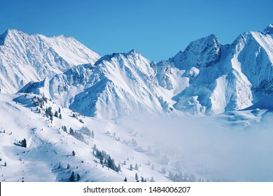 Landscape in Zillertal Arena ski resort in clouds in Tyrol at Mayrhofen in Austria in winter Alps. Alpine mountains with white snow and blue sky. Downhill peaks at Austrian snowy slopes. - Shutterstock ID 1484006207