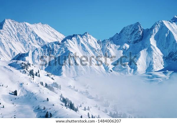 Paysage dans la station de ski Zillertal Arena dans les nuages au Tyrol à Mayrhofen en Autriche dans les Alpes d'hiver. Montagnes alpines avec neige blanche et ciel bleu. Des pics de descente sur les pentes enneigées autrichiennes.