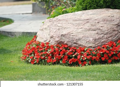 Landscaped flower garden with a rock and red flowers