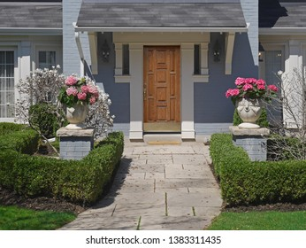 landscaped house front with elegant wooden door and flagstone path
